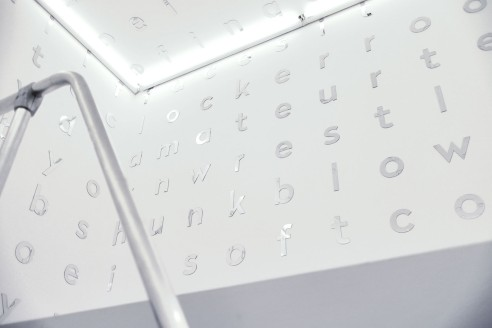 between (legs), 2016, levitating white cube filled with a crossword of porn tags