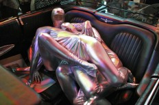 Sculpture of chrome and human matter, 2016, performative sculpture (human printer) distributing the magazine which was the main platform of the exhibition, and squirming on the backseat of a black-as-night Ford Thunderbird
